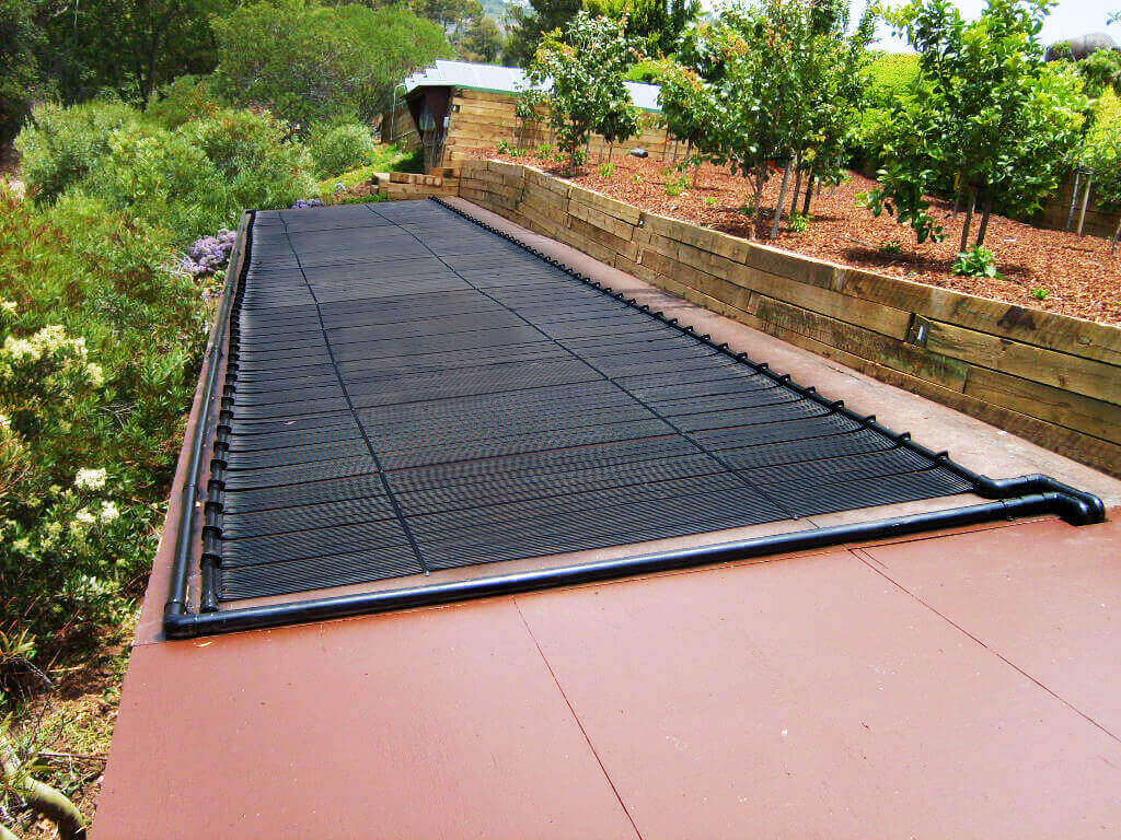Enersol Solar Pool Heaters installed almost flat at on a custom rack surrounded by trees