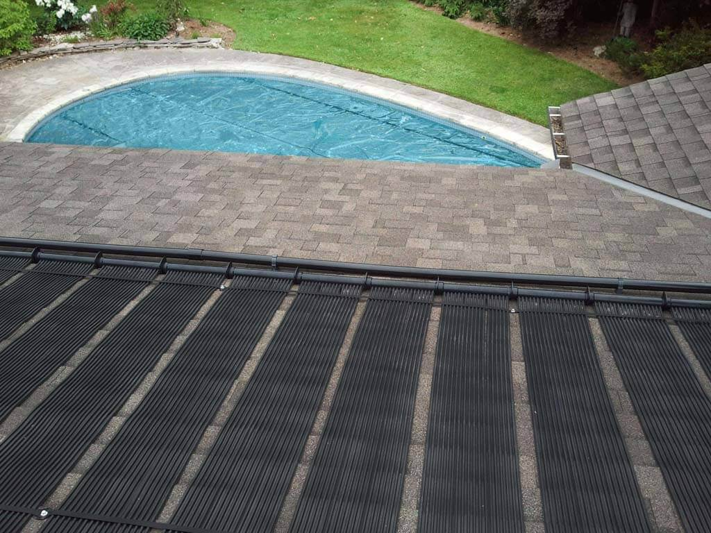 Enersol Solar Pool Heaters installed on the Roof of a house and a view of the inground pool