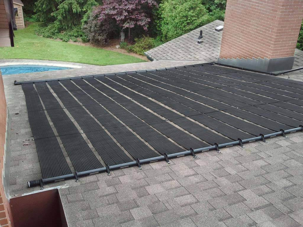 Enersol Solar Pool Heaters on the Roof of a house heating an inground pool