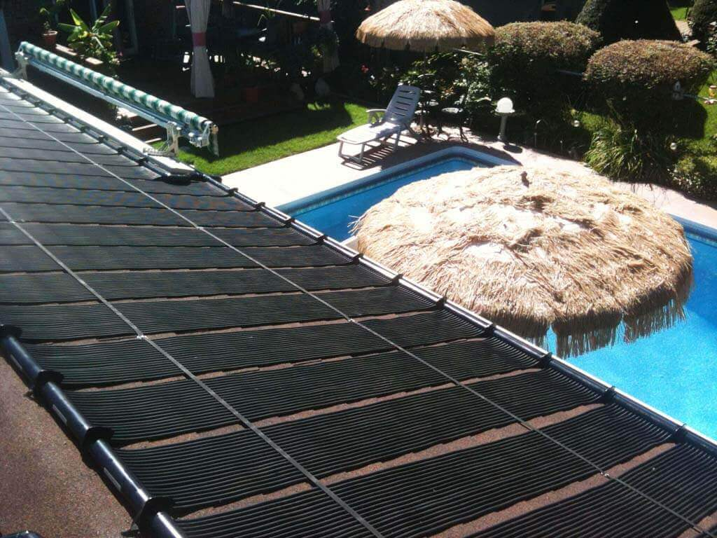 Enersol Solar Pool Heaters and a relaxing in-ground pool with a tiki umbrella