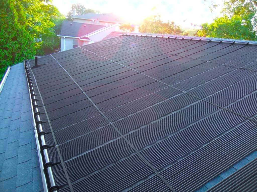 Enersol Solar Pool Heater Residential Roof Installation with tress in a sunny day