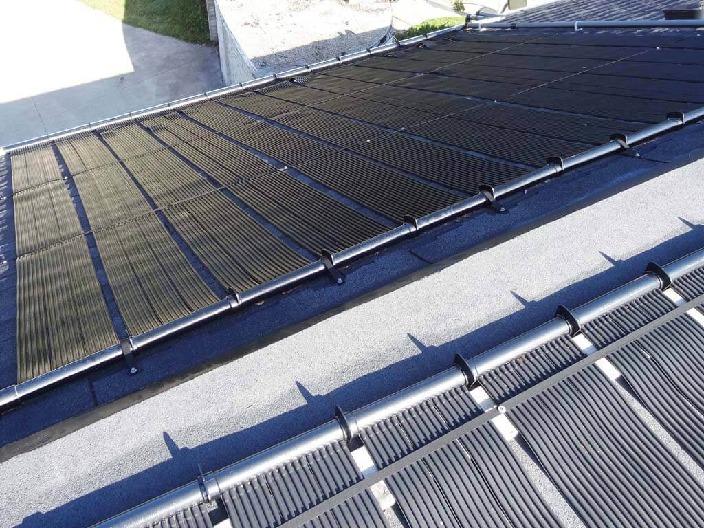 Two banks of Enersol Solar Pool Heaters installed on the Roof of a house heating a concrete inground pool