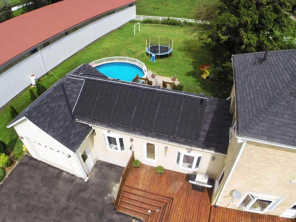 Aerial view of Enersol Solar Pool Heaters installed on the roof of a house and an above-ground pool in the backyard with trampoline