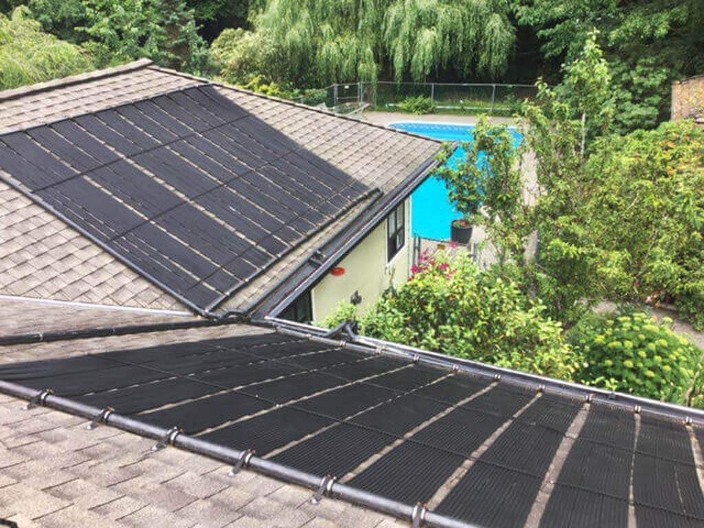 Two banks of Enersol Solar Pool Heaters installed on two roofs of a house and the backyard with an in-ground pool