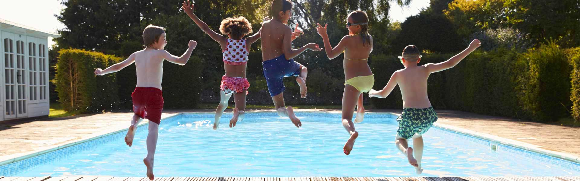 5 young kids jumping into a swimming pool